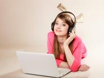 Muchacha con los auriculares y el ordenador portátil que escucha la música Foto de archivo libre de regalías