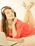 Muchacha con los auriculares y el ordenador que escucha la música Fotografía de archivo