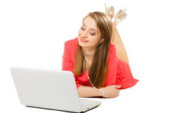 Muchacha con los auriculares y el ordenador que escucha la música Imagenes de archivo