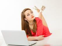 Muchacha con los auriculares y el ordenador que escucha la música Foto de archivo libre de regalías