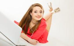 Muchacha con los auriculares y el ordenador que escucha la música Imágenes de archivo libres de regalías