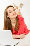 Muchacha con los auriculares y el ordenador que escucha la música Foto de archivo