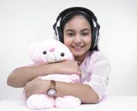 Muchacha con los auriculares y el peluche Fotos de archivo libres de regalías
