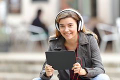 Muchacha con los auriculares y la tableta que le miran Foto de archivo libre de regalías