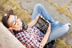 Muchacha con los auriculares y PC de la tableta Imágenes de archivo libres de regalías