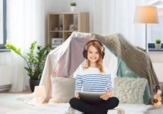 Muchacha con los auriculares y PC de la tableta en casa Fotografía de archivo