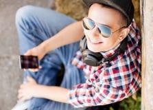 Muchacha con los auriculares y smartphone Imagenes de archivo