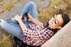Muchacha con los auriculares y smartphone Foto de archivo