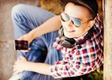 Muchacha con los auriculares y smartphone Foto de archivo libre de regalías
