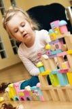 Muchacha con los bloques de madera del juguete Imagenes de archivo
