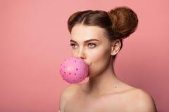 Muchacha con los bollos que soplan el globo Foto de archivo libre de regalías
