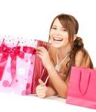 Muchacha con los bolsos coloridos del regalo Foto de archivo