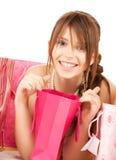 Muchacha con los bolsos coloridos del regalo Fotos de archivo