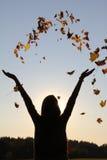 Muchacha con los brazos extendidos, hojas de otoño que lanzan en el cielo Fotografía de archivo libre de regalías