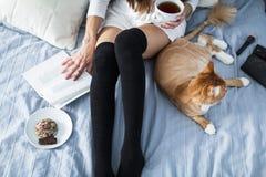 Muchacha con los calcetines calientes con una taza de té, gato, cierre el libro Imágenes de archivo libres de regalías