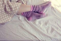 Muchacha con los calcetines rayados rosados, durmiendo en cama Fotos de archivo libres de regalías