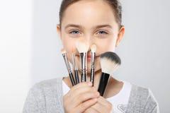 Muchacha con los cepillos para el maquillaje Imagen de archivo libre de regalías