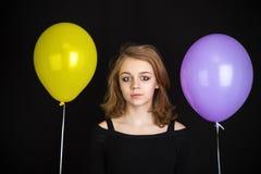 Muchacha con los globos amarillos y púrpuras sobre negro Fotografía de archivo libre de regalías