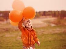 Muchacha con los globos anaranjados al aire libre Foto de archivo libre de regalías