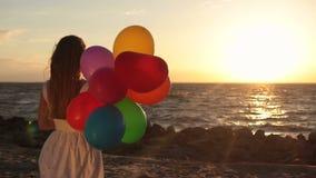 Muchacha con los globos coloridos en la playa en la puesta del sol almacen de metraje de vídeo