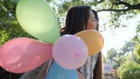 Muchacha con los globos coloridos que dan presentes y que abrazan a la novia al aire libre en el parque, emociones metrajes