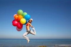 Muchacha con los globos coloridos que saltan en la playa Fotografía de archivo