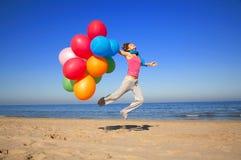 Muchacha con los globos coloridos que saltan en la playa Imagen de archivo libre de regalías