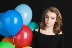 Muchacha con los globos coloridos sobre fondo negro Fotografía de archivo