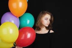 Muchacha con los globos coloridos sobre fondo negro Imagen de archivo libre de regalías