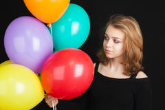 Muchacha con los globos coloridos sobre fondo negro Imágenes de archivo libres de regalías