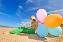Muchacha con los globos coloridos usando la computadora portátil Imagen de archivo libre de regalías