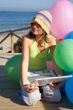 Muchacha con los globos coloridos usando una computadora portátil Foto de archivo