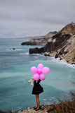 Muchacha con los globos contra el contexto de un mar tempestuoso Fotos de archivo libres de regalías