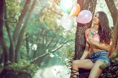 Muchacha con los globos en árbol en naturaleza Fotografía de archivo libre de regalías