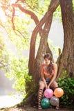 Muchacha con los globos en árbol en naturaleza Foto de archivo