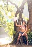 Muchacha con los globos en árbol en naturaleza Imagen de archivo libre de regalías