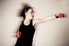 Muchacha con los guantes de boxeo en el movimiento Foto de archivo