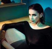Muchacha con los hombros desnudos que mienten en el cuarto de baño con agua púrpura coloreada Concepto de la manera imágenes de archivo libres de regalías