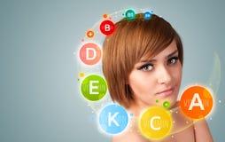 Muchacha con los iconos y los símbolos coloridos de la vitamina Imagen de archivo libre de regalías