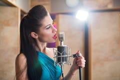 Muchacha con los labios rojos que sostienen un micrófono y que cantan Imagen de archivo libre de regalías