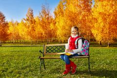 Muchacha con los libros de texto y la taza de café en parque Imagenes de archivo