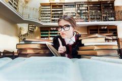 Muchacha con los libros en la biblioteca Foto de archivo libre de regalías