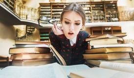 Muchacha con los libros en la biblioteca Imagen de archivo libre de regalías