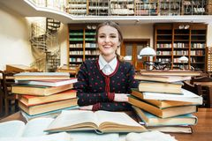 Muchacha con los libros en la biblioteca Fotos de archivo