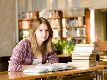 Muchacha con los libros en la biblioteca mirada de la cámara Fotografía de archivo