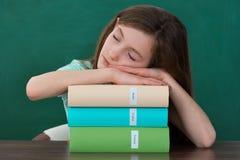 Muchacha con los libros que duerme en el escritorio Imagen de archivo