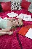 Muchacha con los libros que escucha la música en cama Imágenes de archivo libres de regalías