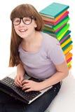 Muchacha con los libros y la computadora portátil del color Fotos de archivo libres de regalías