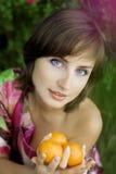 Muchacha con los mandarines Fotos de archivo