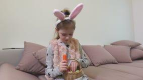 Muchacha con los oídos del conejito y los huevos de Pascua decorativos que come la zanahoria